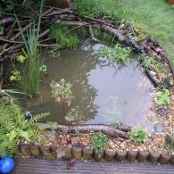 комбинированная отделка берега водоема камнем и деревом
